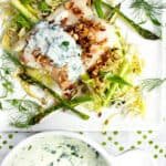 a fillet of baked haddock on a bed of shredded vegetables, topped with yogurt sauce and almond gremolata