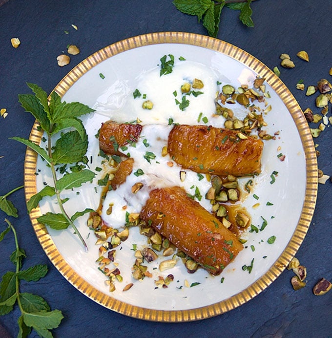 gold rimmed dessert plate with two piece of honey roasted pineapple topped with yogurt, chopped pistachios and chopped mint