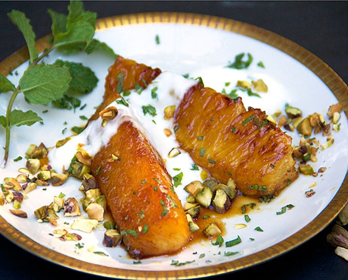 close up of two pieces of honey roasted pineapple on a gold-rimmed plate, topped with yogurt and shopped pistachios