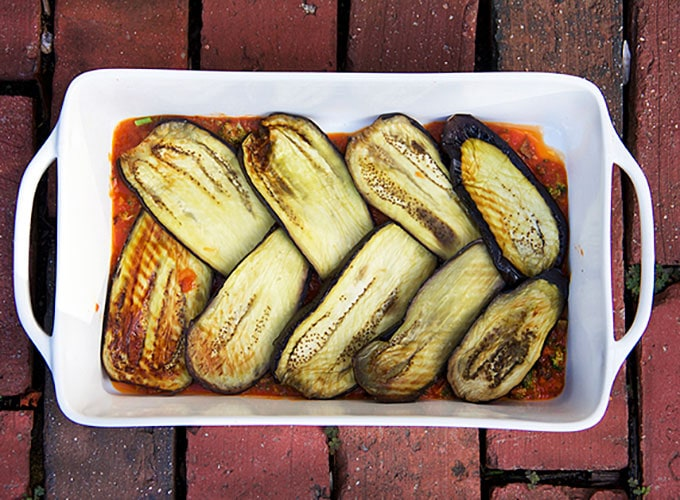 a white casserole with a layer of interwoven baked eggplant slices, showing how to make eggplant lasagna