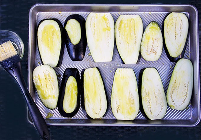 slices of olive oil brushed eggplant on a rimmed baking sheet
