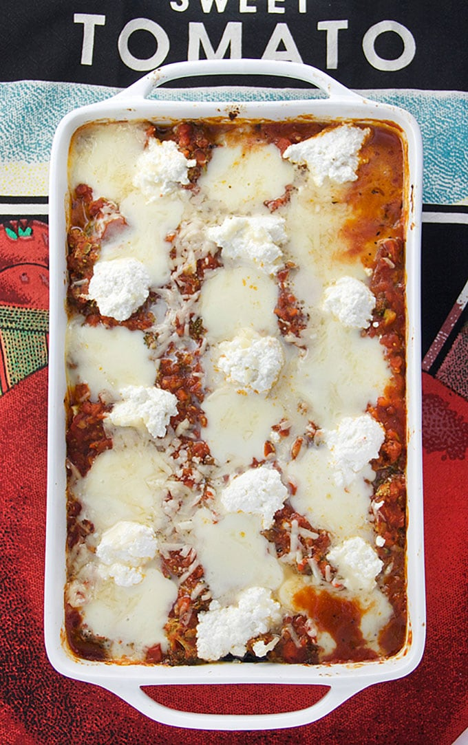 "Overhead view of a rectangular casserole dish on a colorful dish towel that says ""tomato,."" In the casserole is no noodle eggplant lasagna, showing the sauce covered by melted mozzarella cheese and ricotta cheese."