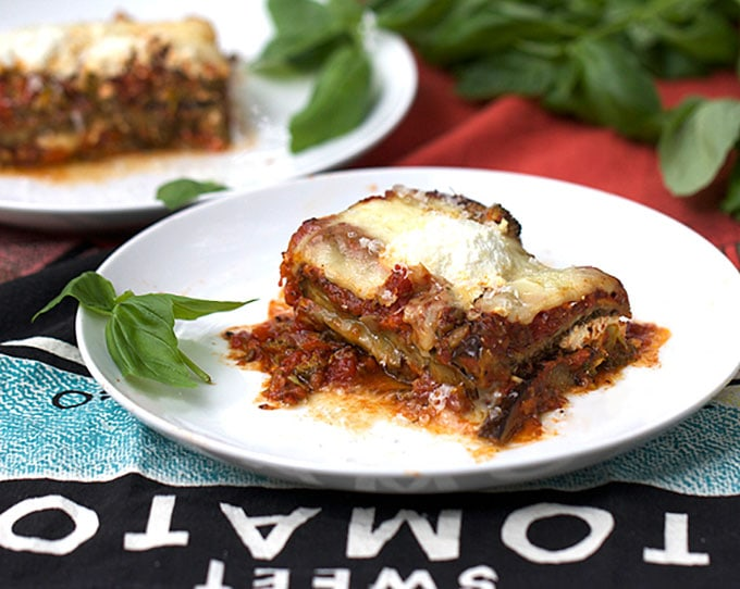 a slice of No Noodle Eggplant Lasagna on a white plate with a basil spring