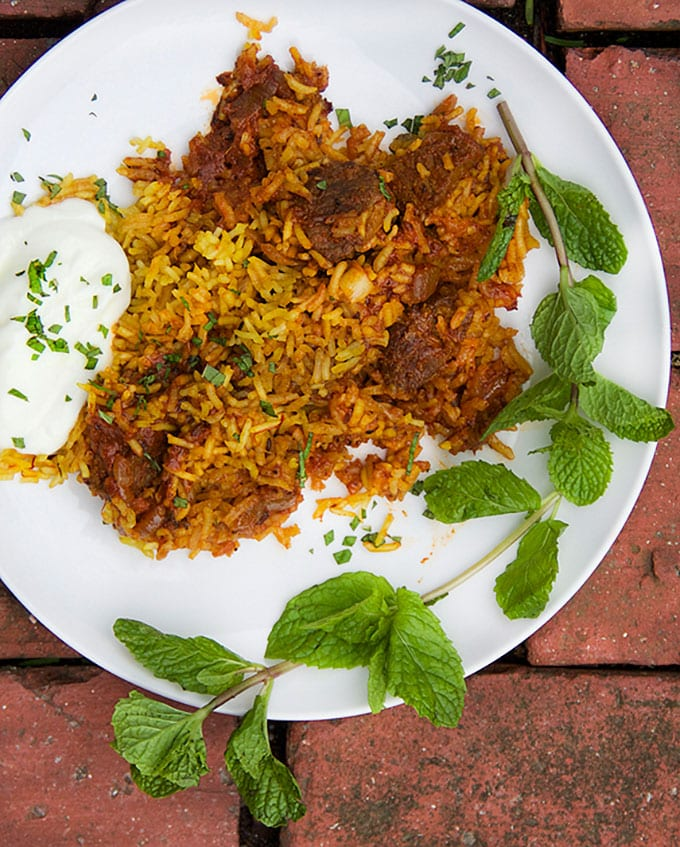 A plate of Indian Lamb Biryani: Sumptuous casserole of tender lamb curry with saffron spiced rice with cucumber-mint raita on the side and a big mint sprig.