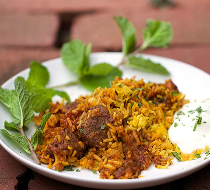 A plate of Indian Lamb Biryani, lamb and rice casserole, with cucumber raita on the side and a large sprig of mint to garnish.