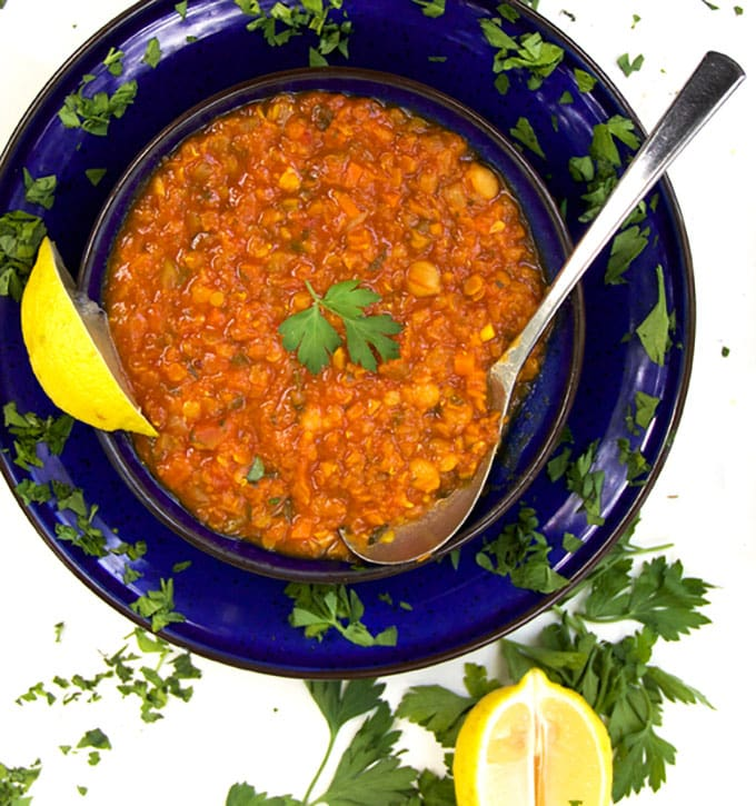 blue bowl filled with red lentil soup with chickpeas, a spoon, a lemon wedge and sprinkles of parsley
