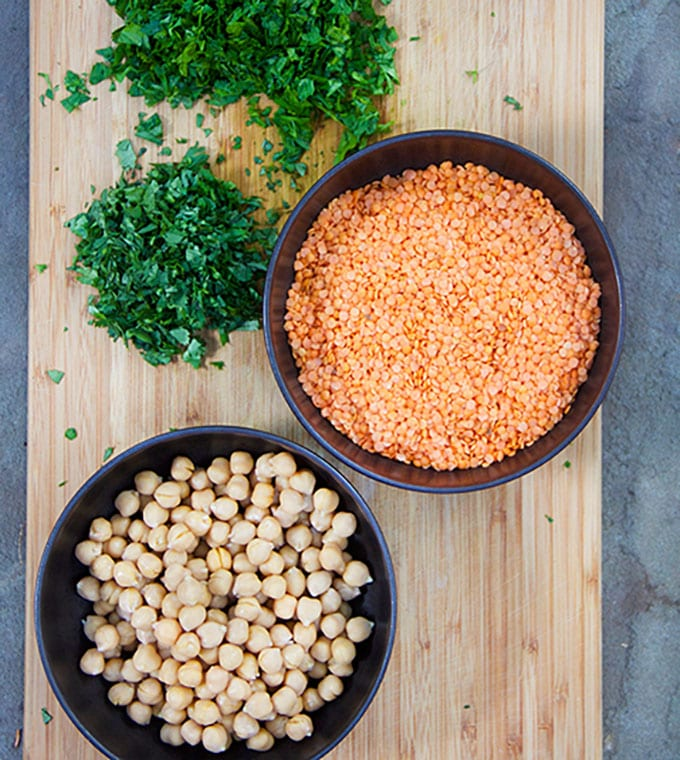 wooden cutting board topped with chopped herbs and two bowls, one filled with chickpeas the other with raw red lentils