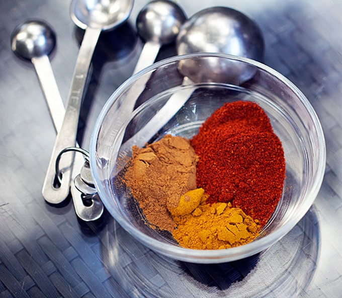 measuring spoons and a glass bowl with three different spices, turmeric, cinnamon and chili powder