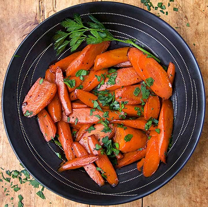 black bowl with glazed carrots and a garnish of chopped parsley