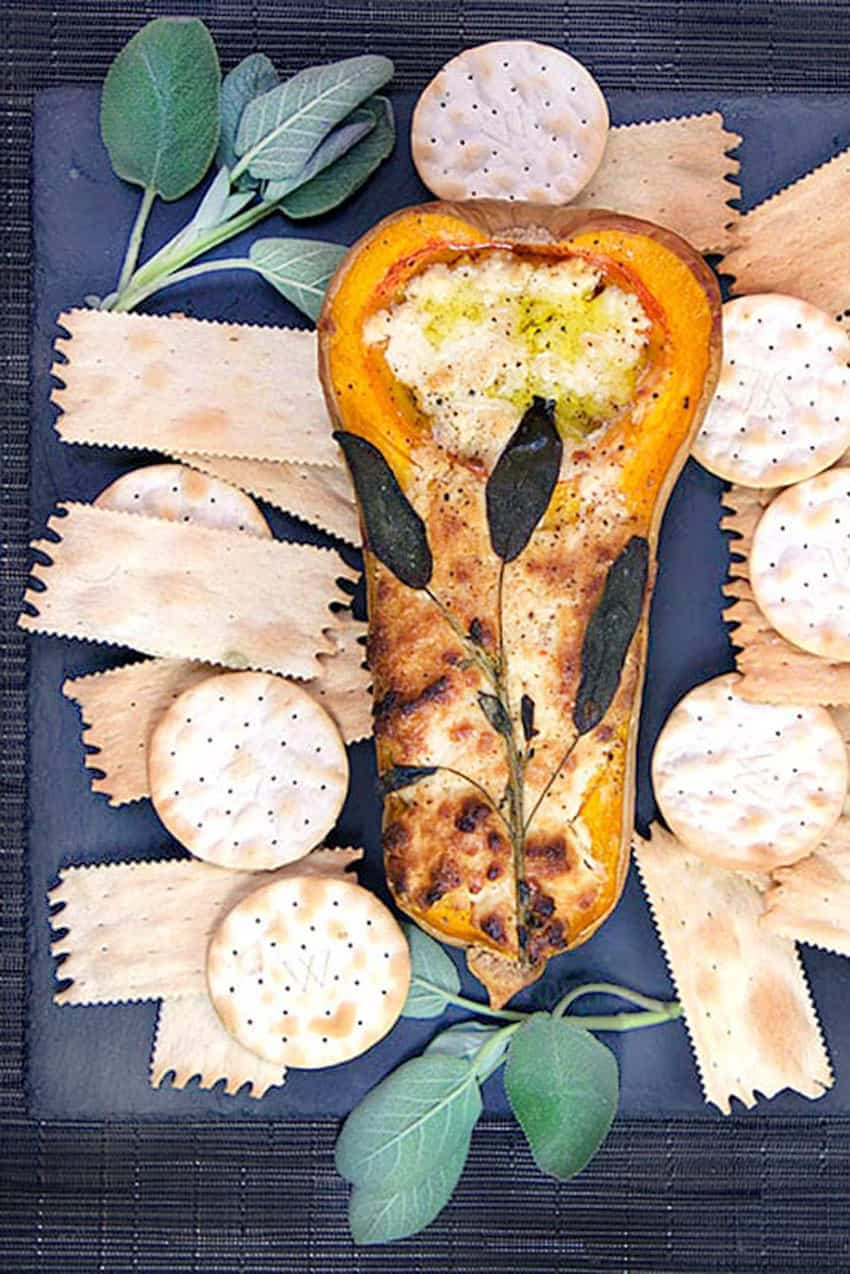 half a roasted butternut squash stuffed with blue cheese, topped with sage leaves and surrounded by crackers