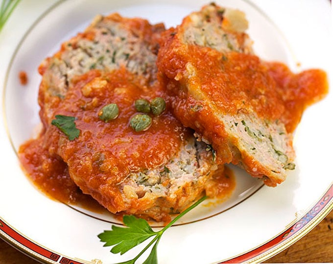 Two slices of Sicilian Turkey Meatloaf with tomato sauce poured over it and a few capers.
