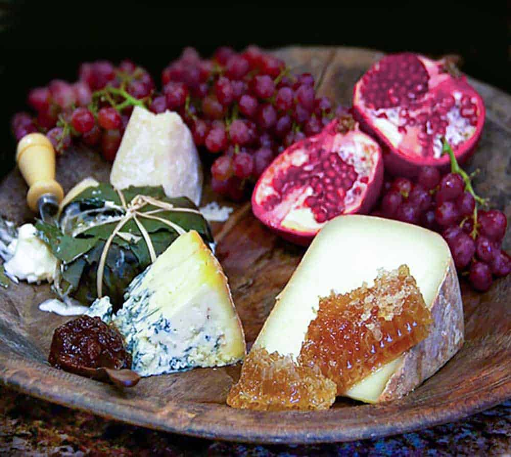dark brown wooden cheese platter topped with cheeses, grapes, honeycomb and a halved pomegranate