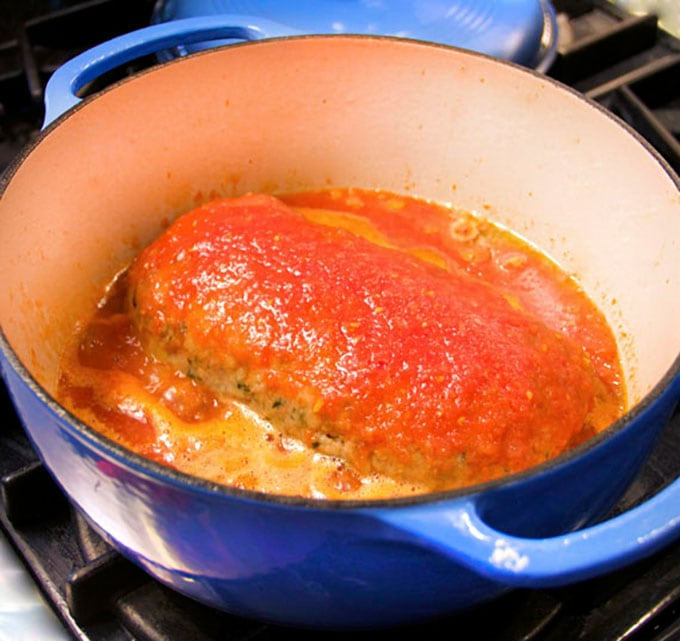 simmering the meatloaf in wine-scented tomato sauce