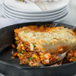 cast iron skillet with a large piece of shepherd's pie in it and a stack of plates and forks in the background