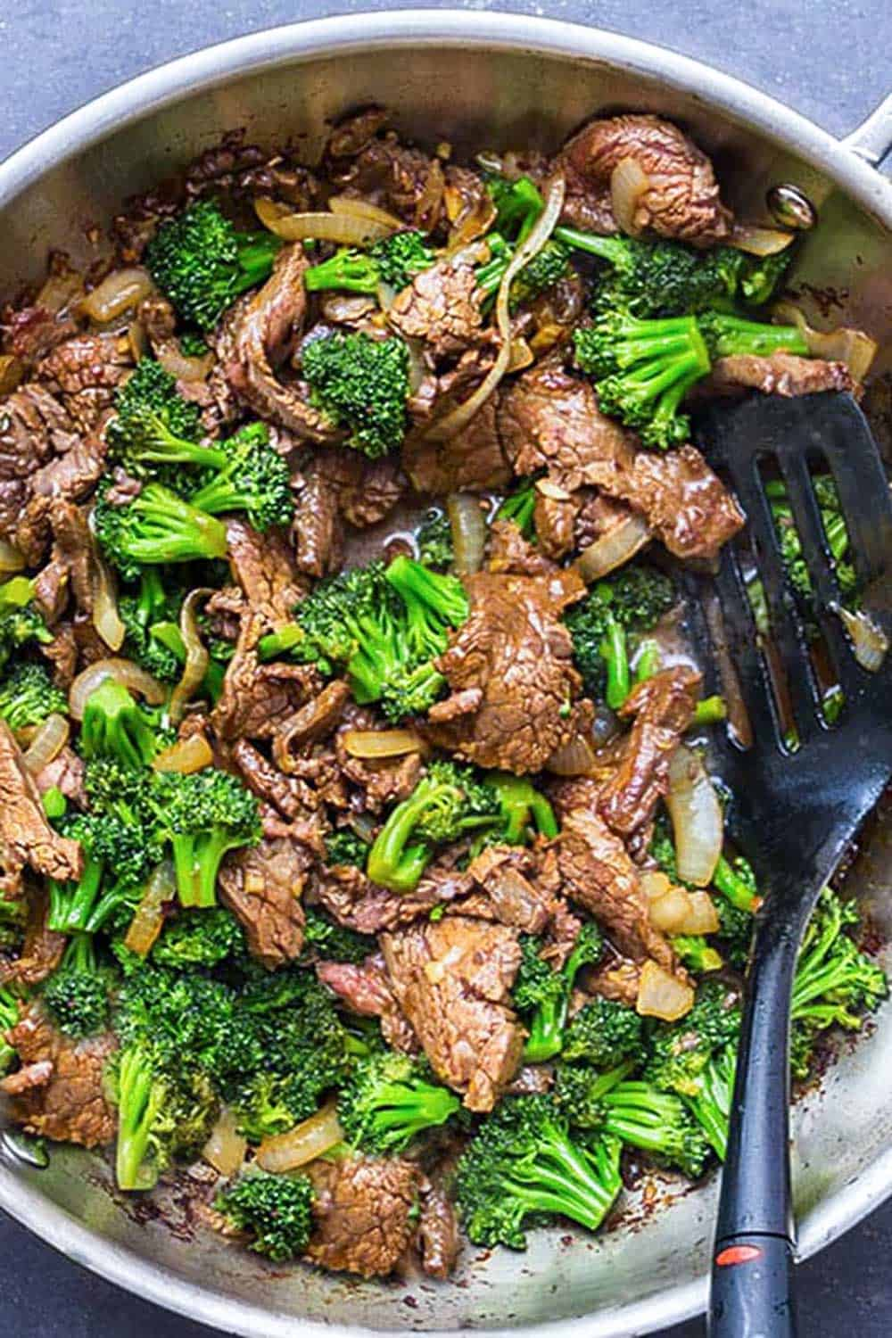 overhead shot of Chinese Beef and Broccoli in a wok with a black spatula