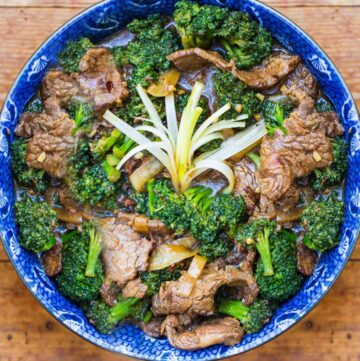 overhead shot showing a blue bowl filled with Chinese beef and broccoli stir fry. A spray of scallions in the center to garnish