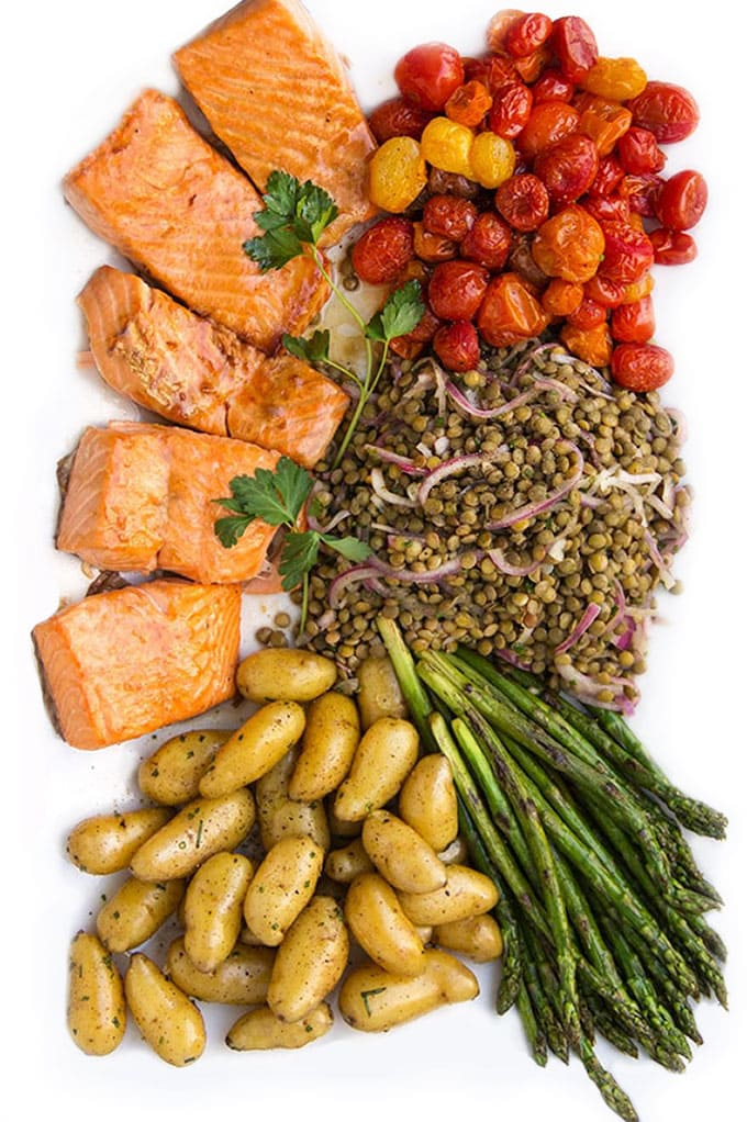 a composed salads on a white platter with five pieces of broiled salmon fillet, roasted cherry tomatoes, french lentils, sautéed thin asparagus and herbed fingerling potatoes