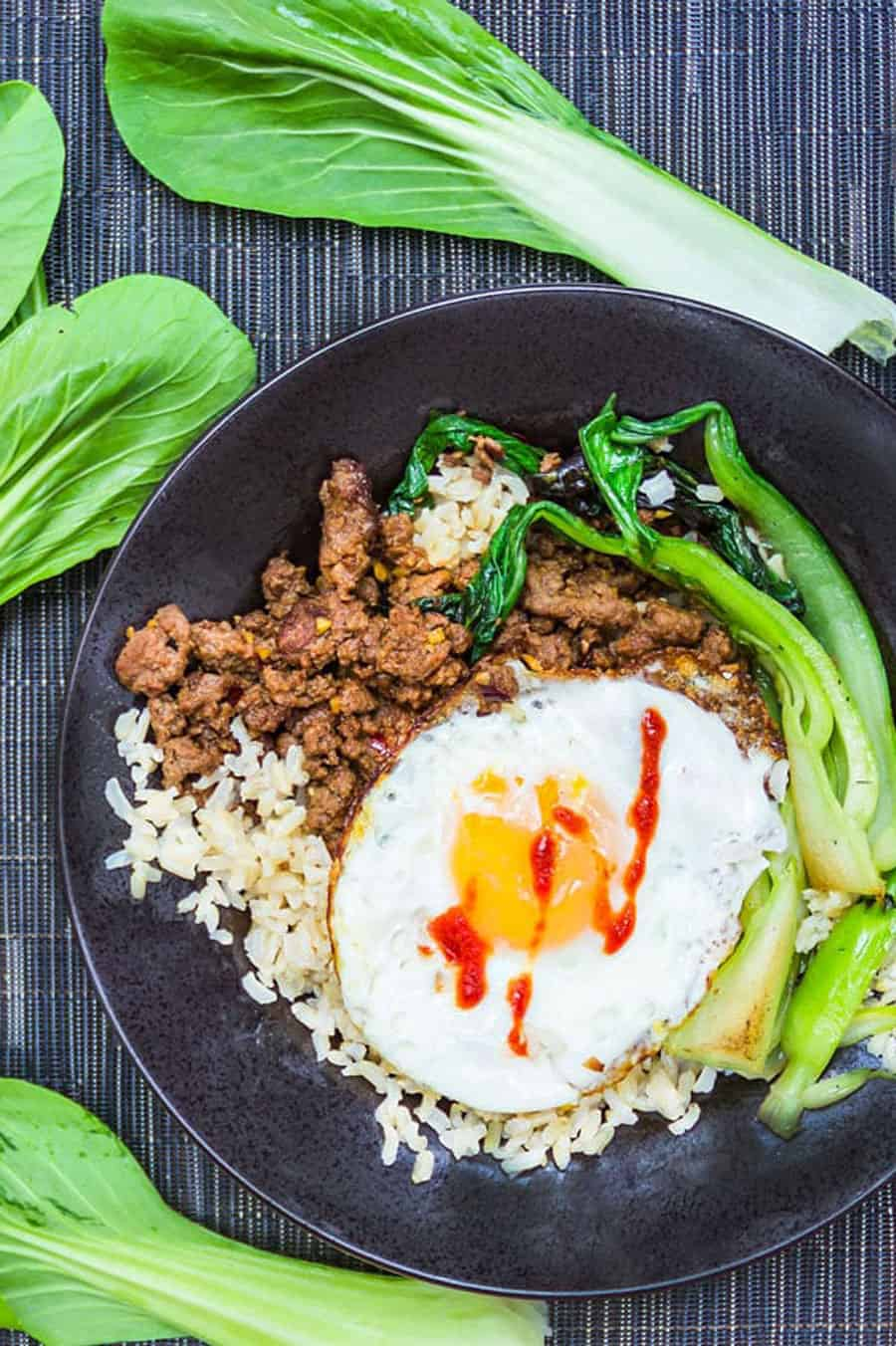 Thai Beef Rice Bowl in a shallow black bowl with stir-fried ground beef, brown rice, sautéed bok choy, and a fried egg on top. leaves of raw bok choy surround the plate.