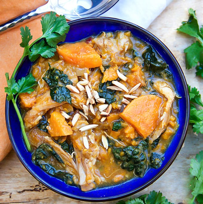 This Moroccan Chicken Stew is a one-pot dinner with fall-apart tender chicken thighs, sweet potatoes, dried apricots and kale, oven-braised in chicken and broth aromatic spices. [paleo] [gluten-free, dairy-free] l panningtheglobe.com