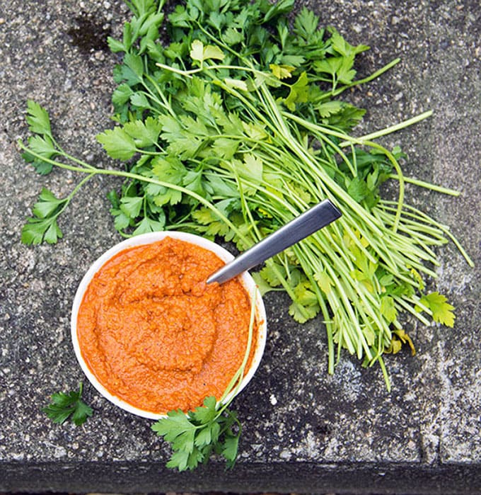 Spanish Romesco Sauce in a small bowl next to a big pile of parsley