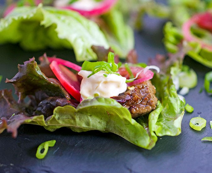 These Korean Beef Lettuce Wraps are an explosion of flavor. Famously delicious Korean Bulgogi beef wrapped up in lettuce leaves with homemade picked onions and radishes and miso mayonnaise. Serve as an appetizer or main dish l Panning The Globe Recipe
