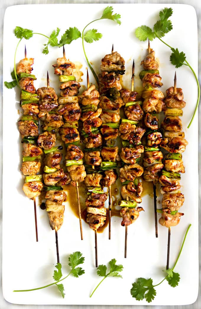 8 skewers of grilled yakitori chicken and scallion skewers on a white platter garnished with sprigs of cilantro