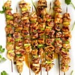 8 skewers of yakitori chicken with scallions, and sprigs of cilantro decorating the edges