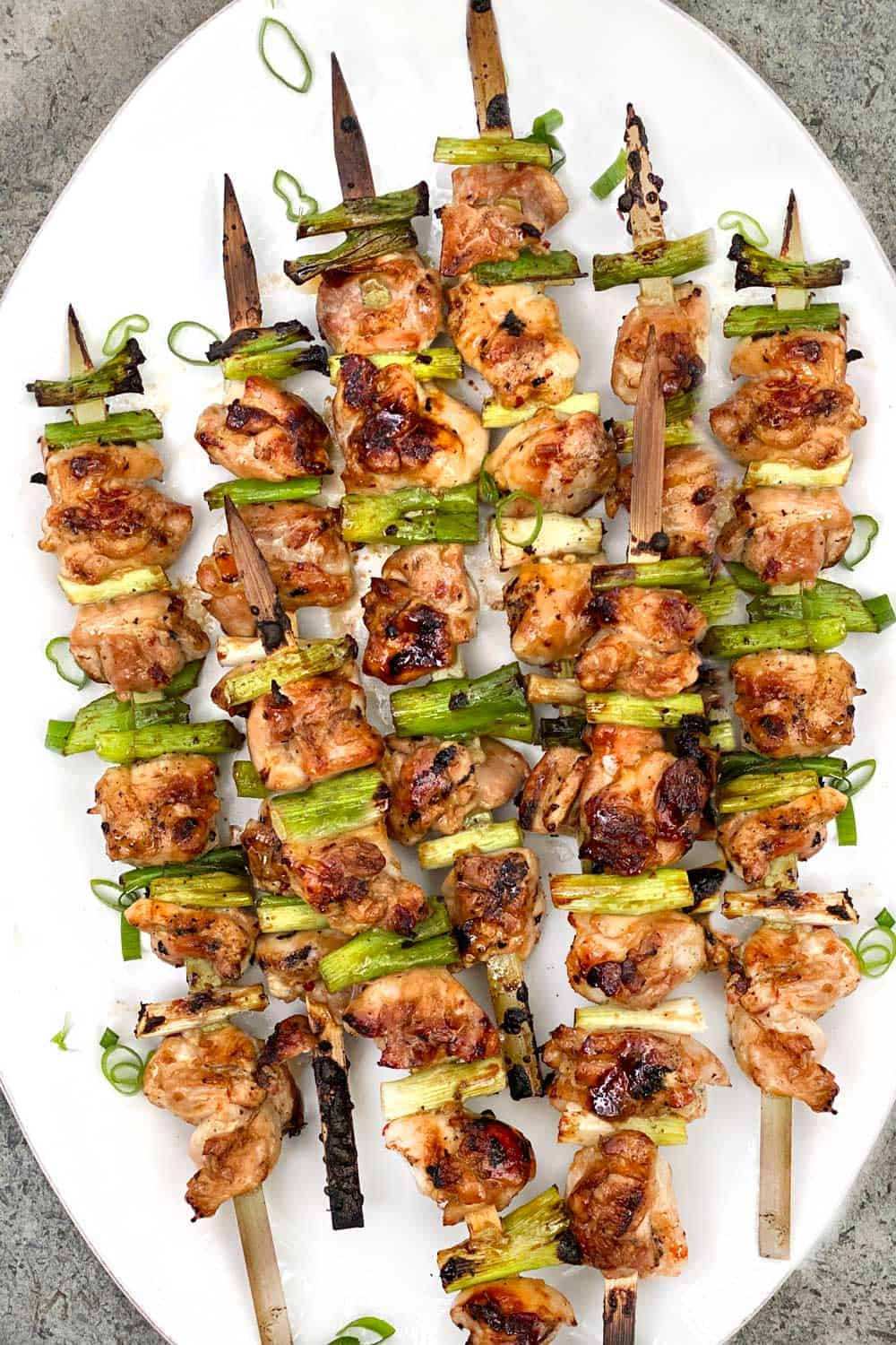 8 yakitori chicken and scallions skewers on a white oval platter