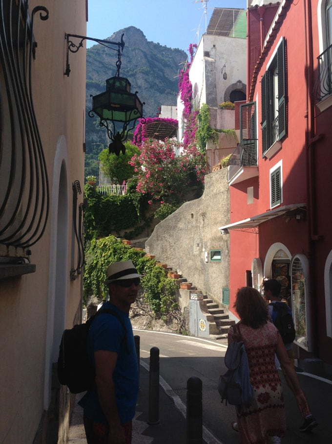 A scene in Positano Italy, looking down a narrow road with colorful buildings and a mountain in the distance.