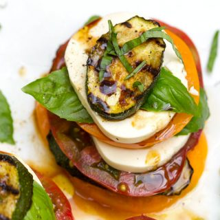 Here's a delicious and fun twist on the classic Italian Caprese Salad recipe. Grilled zucchini is added to the mix and everything is arranged in stacks. It's an easy appetizer recipe that looks elegant. Or serve it for lunch or brunch l www.panningtheglobe.com