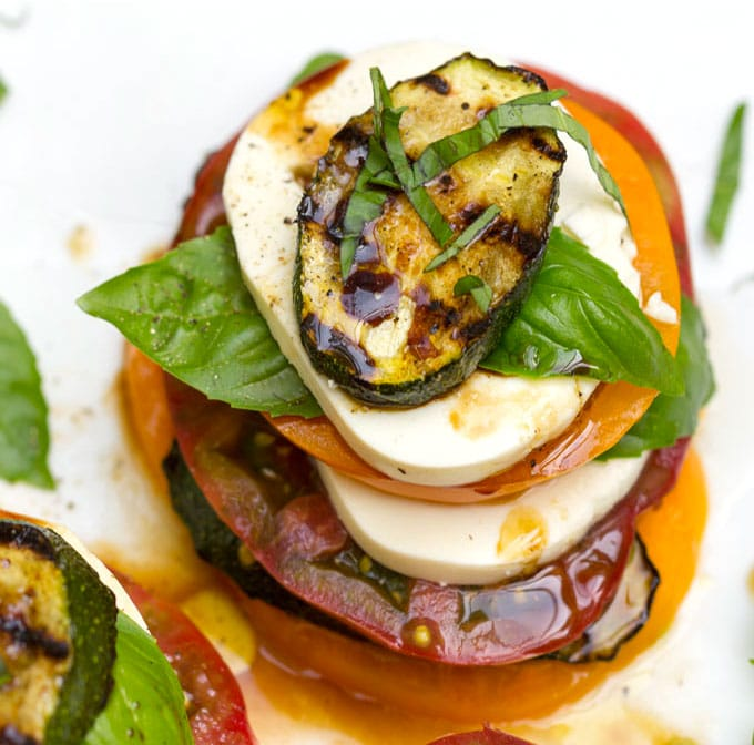 A stacked up caprese salad with layers of tomato, basil, mozzarella and grilled zucchini