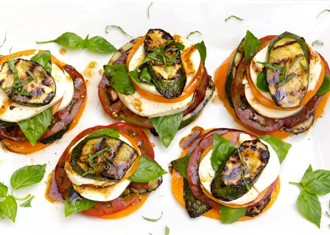 5 zucchini caprese salad stacks on a white platter with sprigs of basil strewn around