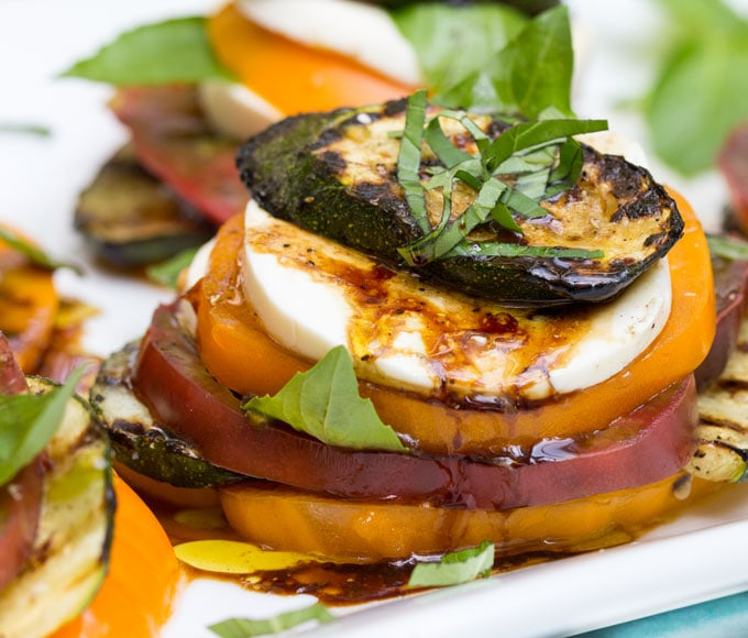A close up of a grilled zucchini caprese salad stack with drizzles of olive oil and balsamic and slivered basil on top