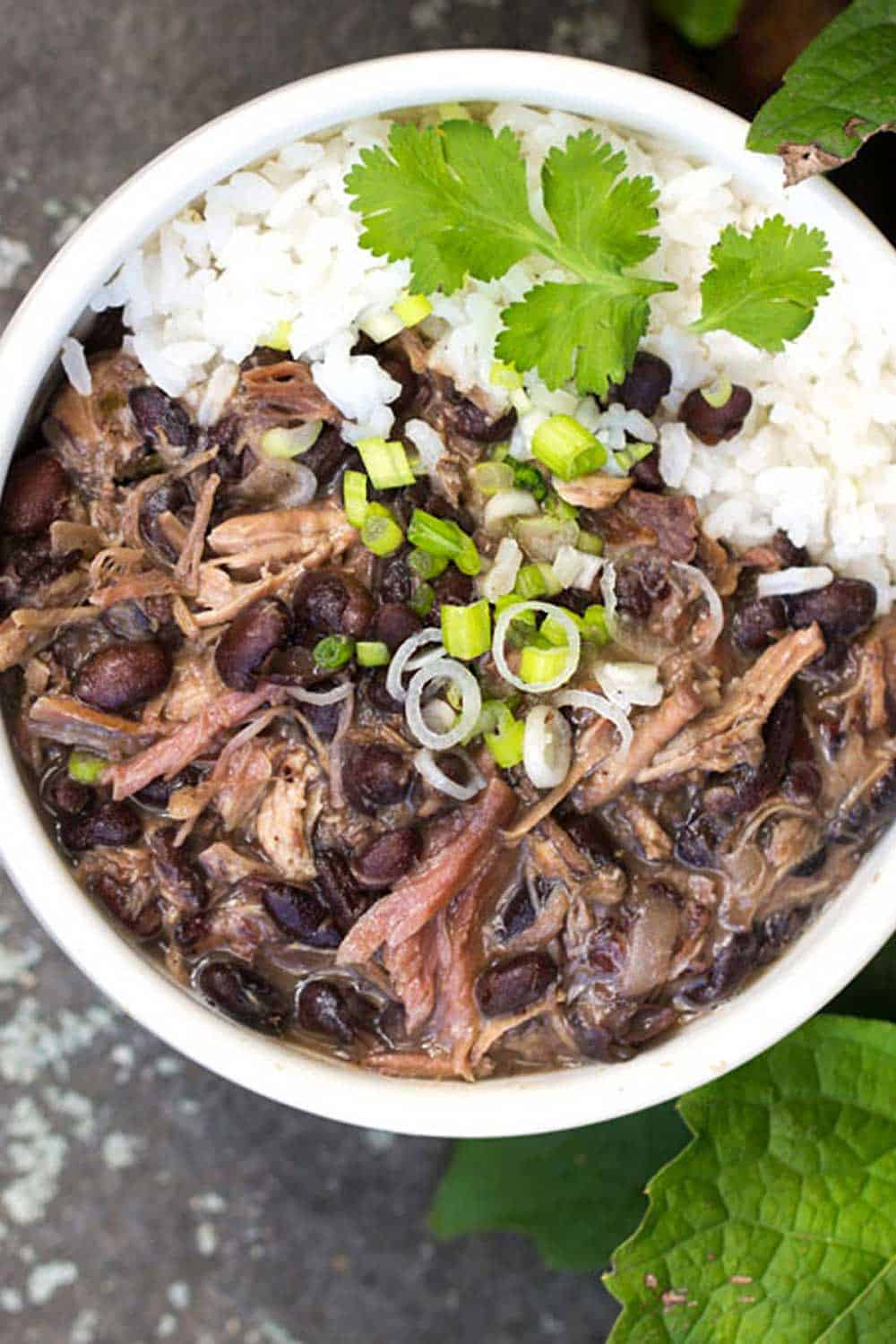 Slow cooker Brazilian Feijoada, Brazil's famous meat and bean stew, with rice, in a white bowl