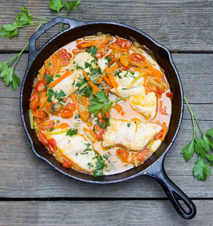 Cast iron skillet filled with fish, sliced vegetables, tomatoes and water. Garnished with parsley.