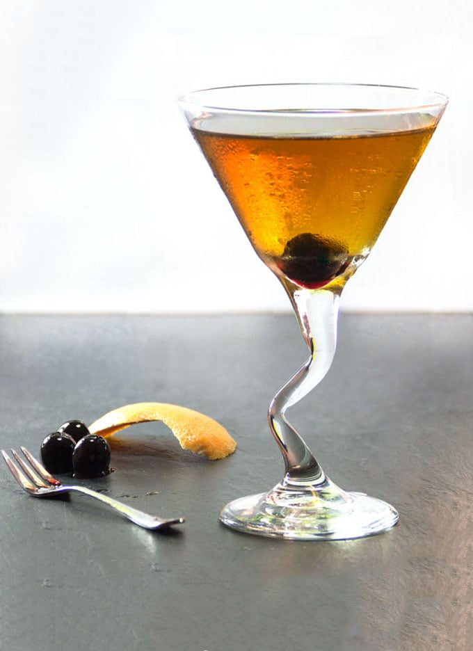A martini glass with a perfect manhattan and cherries and orange zest