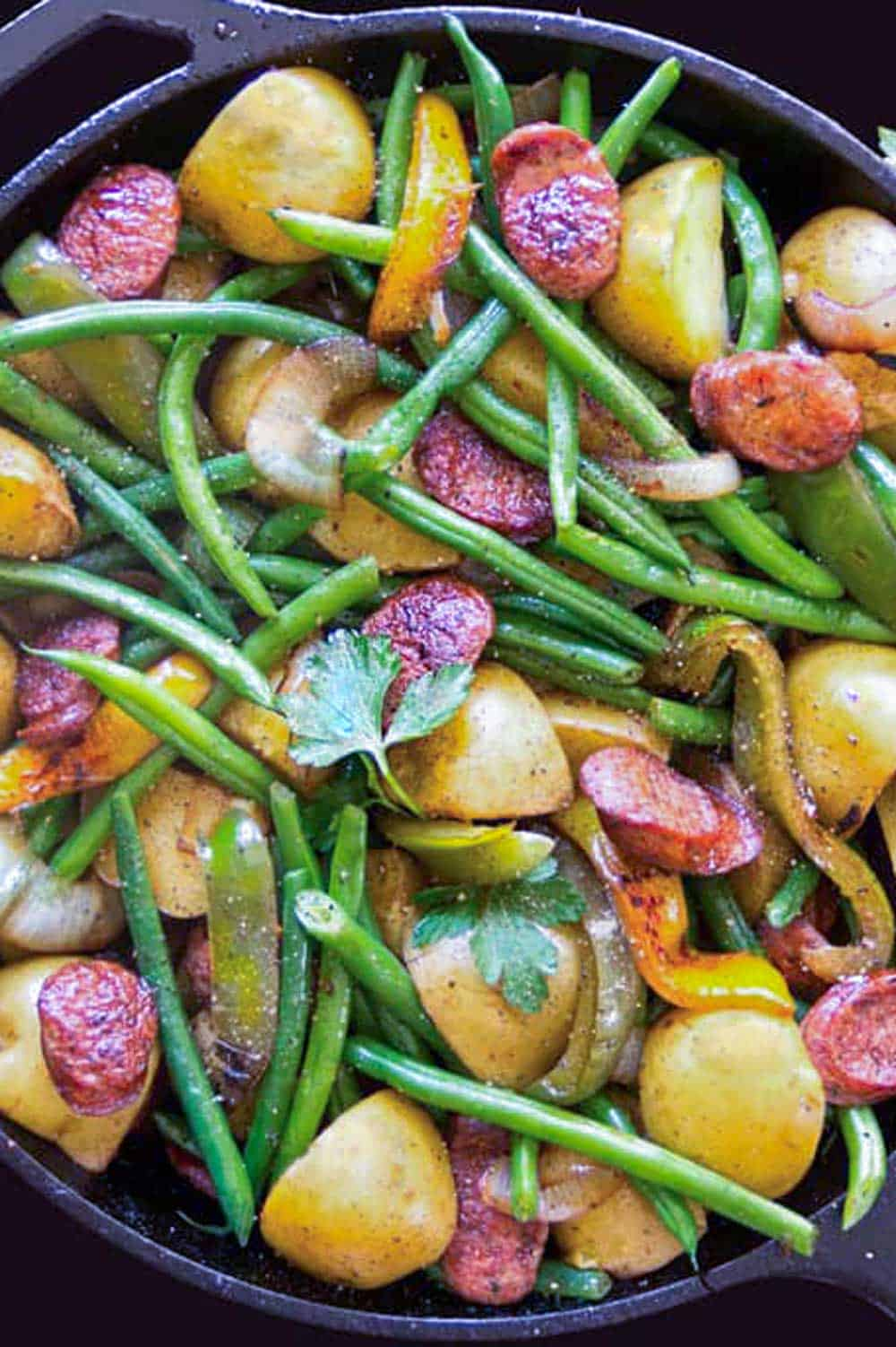 close up of sausage peppers potatoes onions and green beans