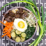 Bibimbap • Korean rice bowl with marinated beef, assorted vegetables, fried egg, spicy sauce • Panning The Globe