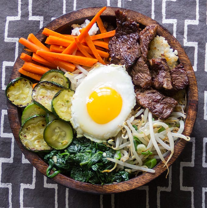 It's easy to make Korean bibimbap at home, a bountiful rice bowl with delicious Bulgogi beef, loads of vegetables, spicy sauce and a fried egg on top l Panning The Globe Recipe