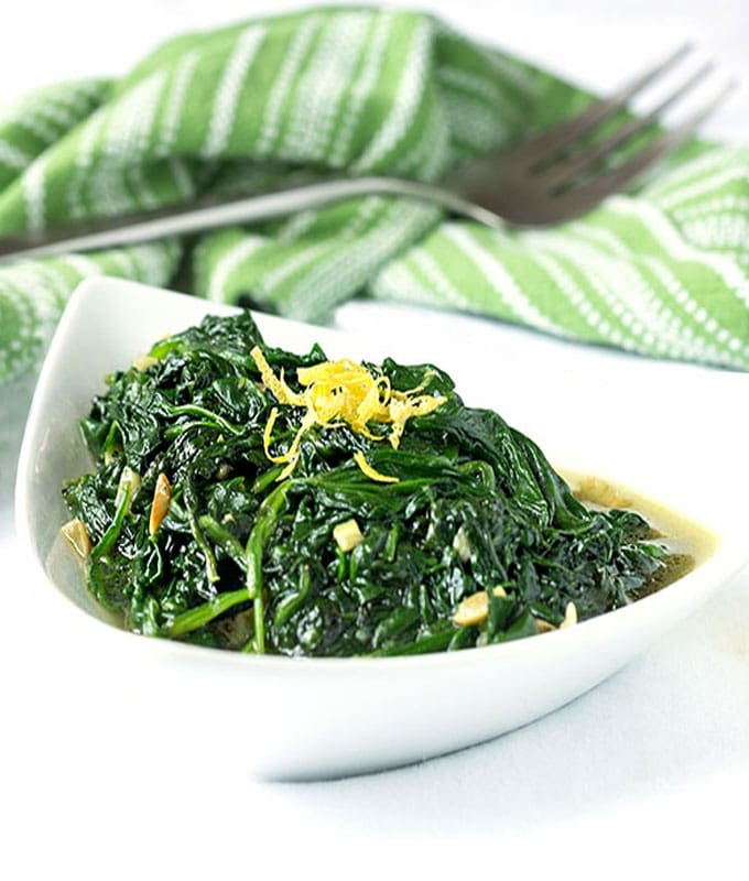 Sautéed Spinach and Garlic in a bowl topped with lemon zest.