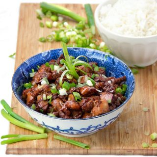 Asian honey soy chicken in a bowl sprinkled with scallions.