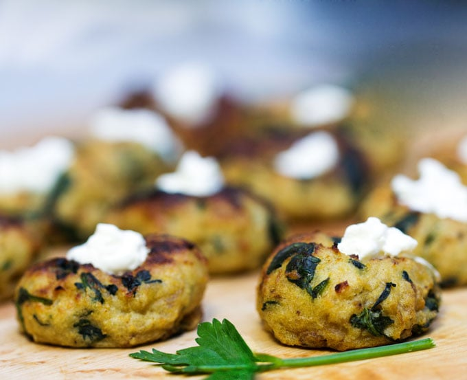 Mini Spinach Potato Knish Appetizer topped with sour cream.