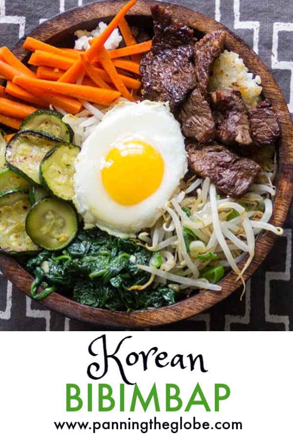 bibimbap bowl with bulgogi beef, carrots sticks, sautéed sliced zucchini, spinach, bean sprouts, and a fried egg in the middle