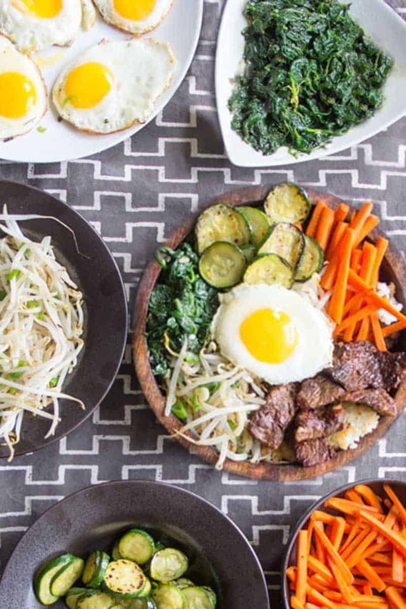 8 bowls of ingredients for bibimbap set out on a grey patterned tablecloth: spinach, bean sprouts, carrots, zucchini, rice, fried eggs, bulgogi beef, and a complete bibimbap bowl