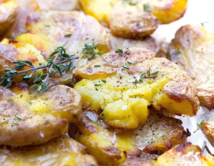 These smashed potatoes are so incredibly good, crisp outside, tender inside, topped with olive oil and spices or anything else you can dream up. The recipe is easy: boil, smash, add toppings, and crisp in the oven. These are perfect for company. They're always a huge hit, plus you can boil and smash them ahead of time.
