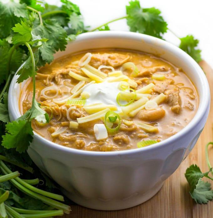Bowl of white chicken chili with sour cream, cheese and scallions