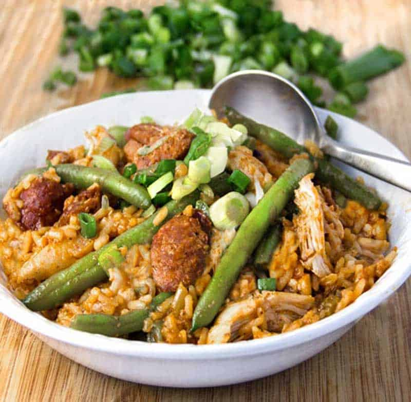 a bowl of spicy chicken jambalaya with sausages and green beans