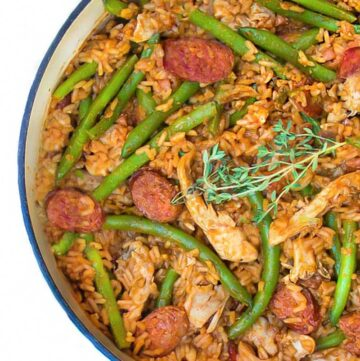 close up looking down into a white pot of spicy chicken jambalaya with sausages and green beans