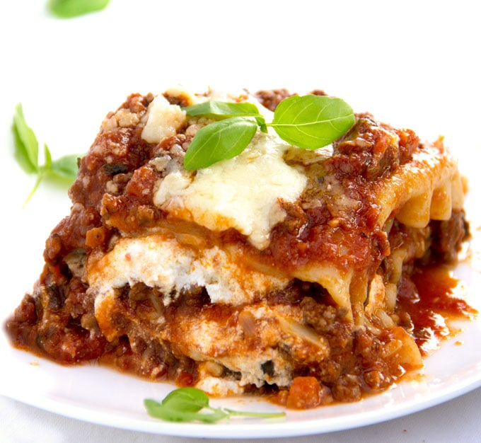 close up of a square of meaty, cheesy, tomatoey lasagna with sprigs of basil on top and scattered around