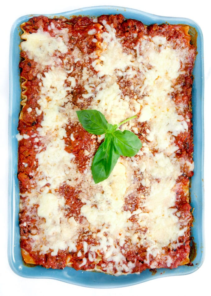 a blue rectangular casserole filled with cheesy lasagna and a sprig of basil in the middle